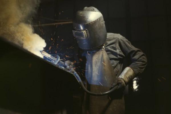 Un ouvrier manipulant des composants abrasifs